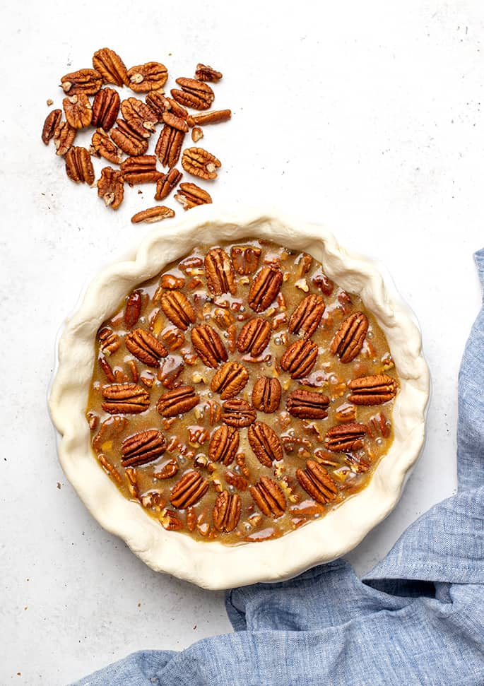 Overhead image of raw gluten free pecan pie with extra pecans on white surface and blue cloth