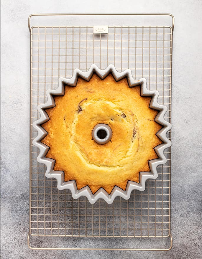 Overhead image of top of yellow cake in bundt pan on wire rack on white surface