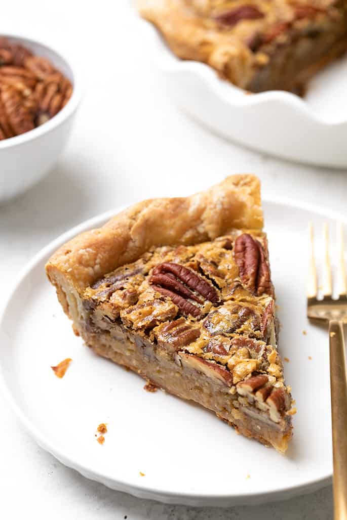 Slice of gluten free pecan pie on small white plate with rest of pie in background in white pie plate and small white bowl with pecans