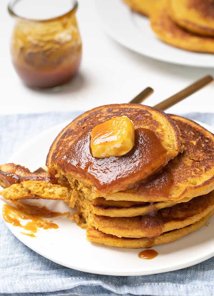 Stack of 5 pumpkin pancakes on white plate with pat of butter on top with bite on fork