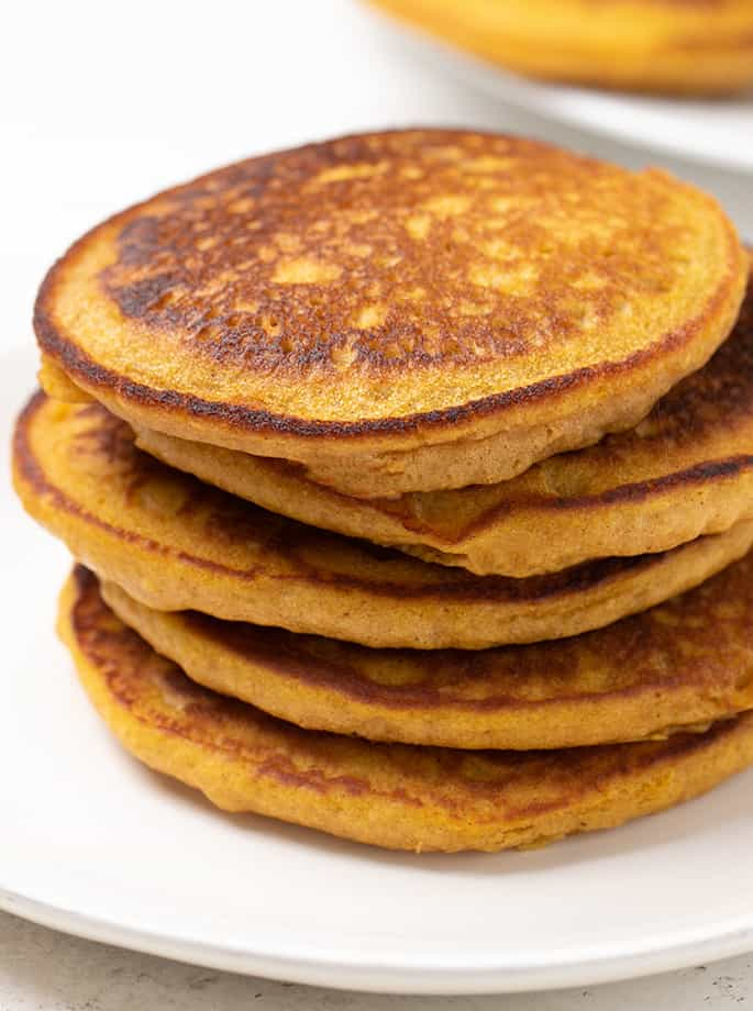 Stack of 5 pumpkin pancakes on white plate