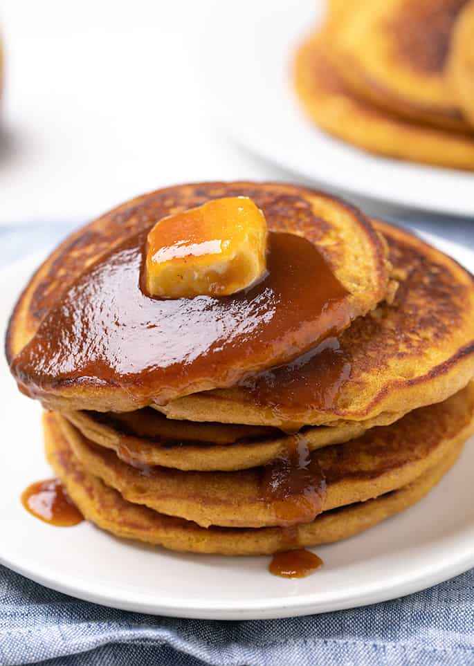 Stack of 5 pumpkin pancakes with pat of butter on top and syrup dripping from top down sides on white plate on blue cloth