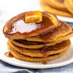 Small image of stack of pumpkin pancakes with pat of butter and syrup on white plate