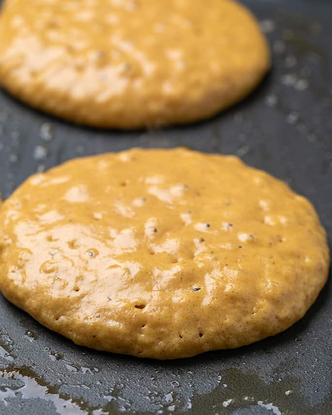 Two raw but nearly set pumpkin pancakes on black griddle with butter
